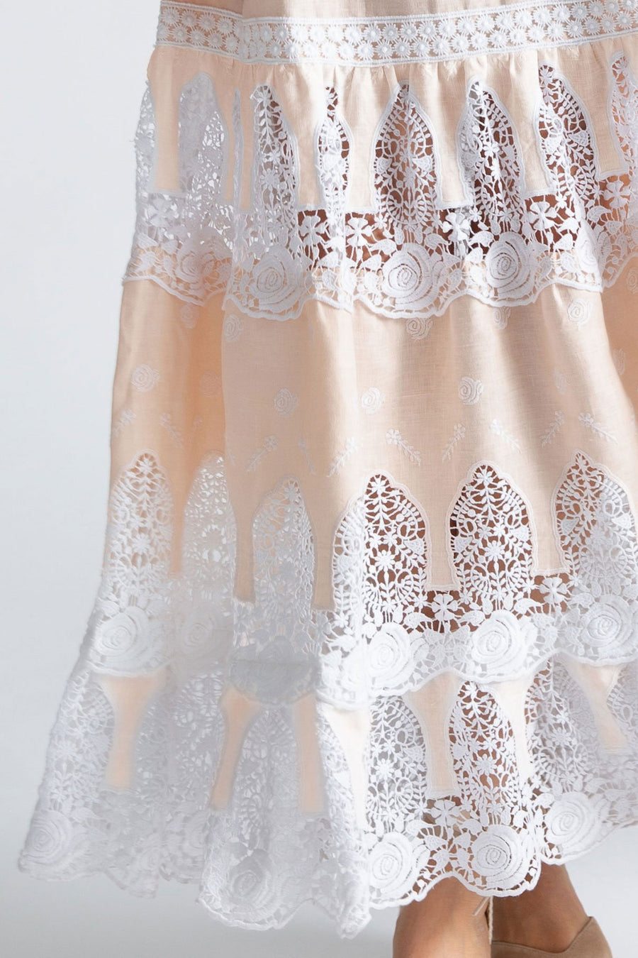 This is a detail photo of a linen and lace gown with 3 tiers of lace embroidery at the bottom. The detail of lace here shows the floral designs and honey color of the linen on the dress.