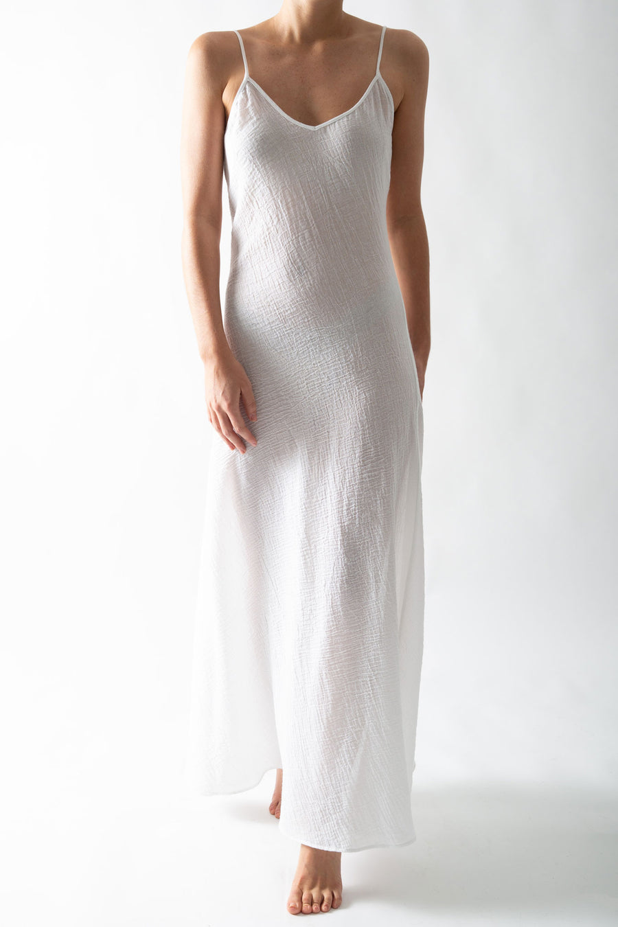 This is a photo of a woman wearing a sheer white slip dress in a cotton gauze material.