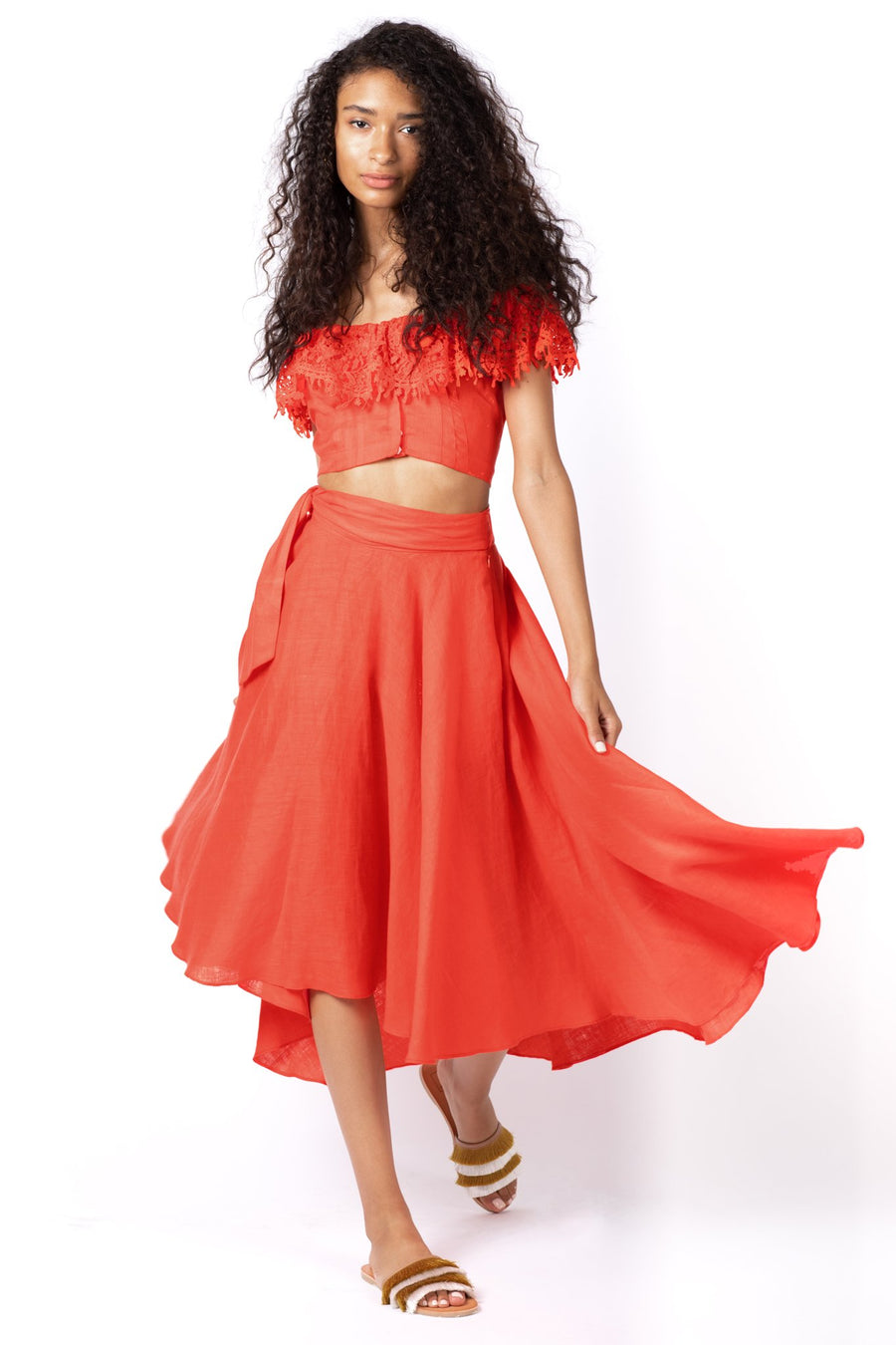 This is a photo of a woman wearing a bright red, lace trimmed, off the shoulder, linen top. Paired with a matching bright red, calf length, linen skirt.