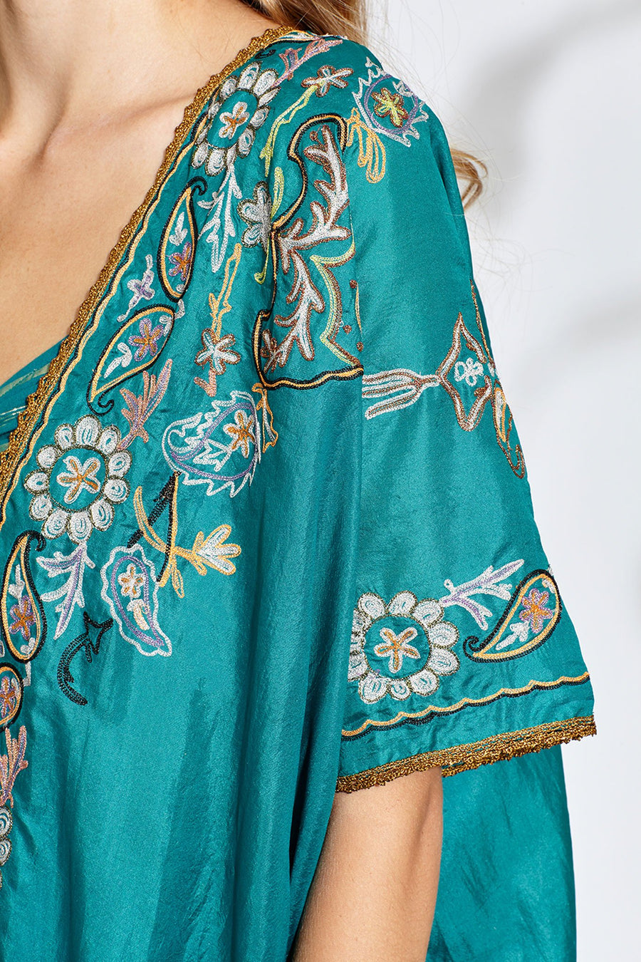 This is a detail photo of the sleeve of a lagoon-colored silky coat with colorful embroidery. The embroidery has paisley and floral designs and sleeve hem is finished with gold trim.