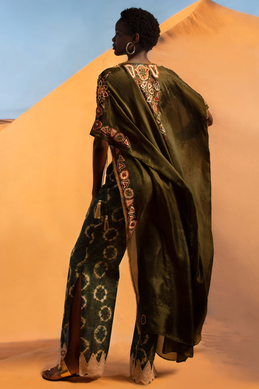 This is a photo of a woman wearing a silky dark green coat with colorful embroidery down the center back and along the armhole and side seams. She faces backwards and sticks one leg out to show her tie-dye inspired shibori printed pants with side left slit.