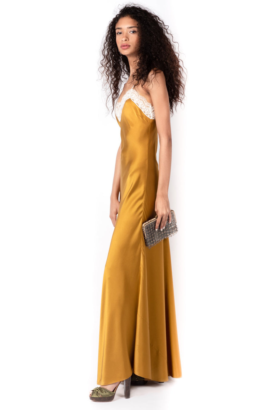 This is a photo of a woman wearing a floor length, gold colored, silk charmeuse slip dress. The dress has a delicate, ivory trim around the neckline and a high slit on the left side.