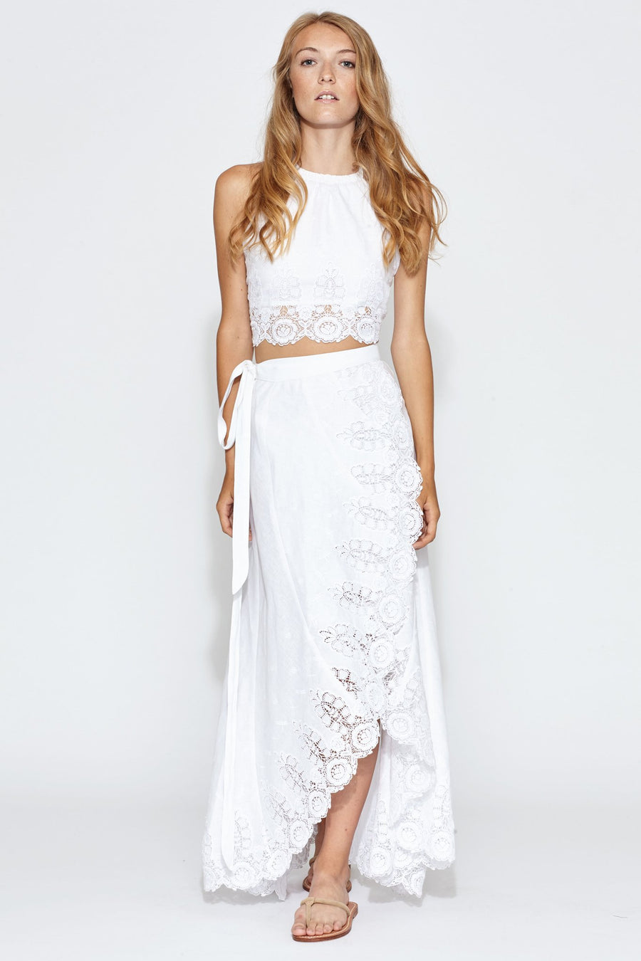 This is a photo of a woman wearing a white linen and lace two piece set with halter crop top and wrap maxi skirt with tie on one side.