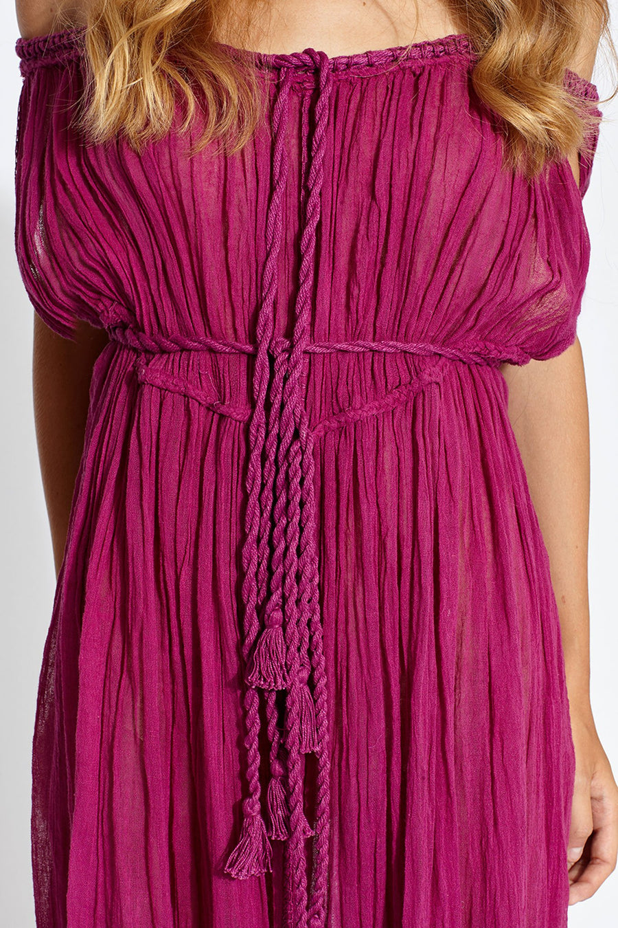 This is a detail photo of a magenta cotton gauze coverup dress with rope and tassel ties around center front and waist.