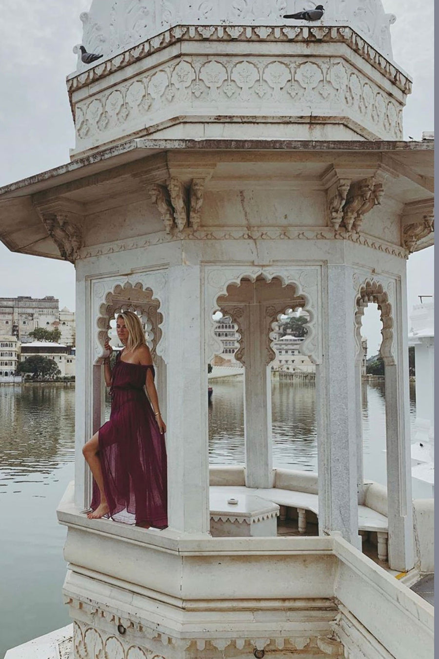 This is a photo of a woman wearing a magenta cotton gauze floor-length maxi coverup that falls off both shoulder and ties around center front chest area and waistline. Photo is taken on a white gazebo type structure overlooking a body of water and dress shows center front leg slit.