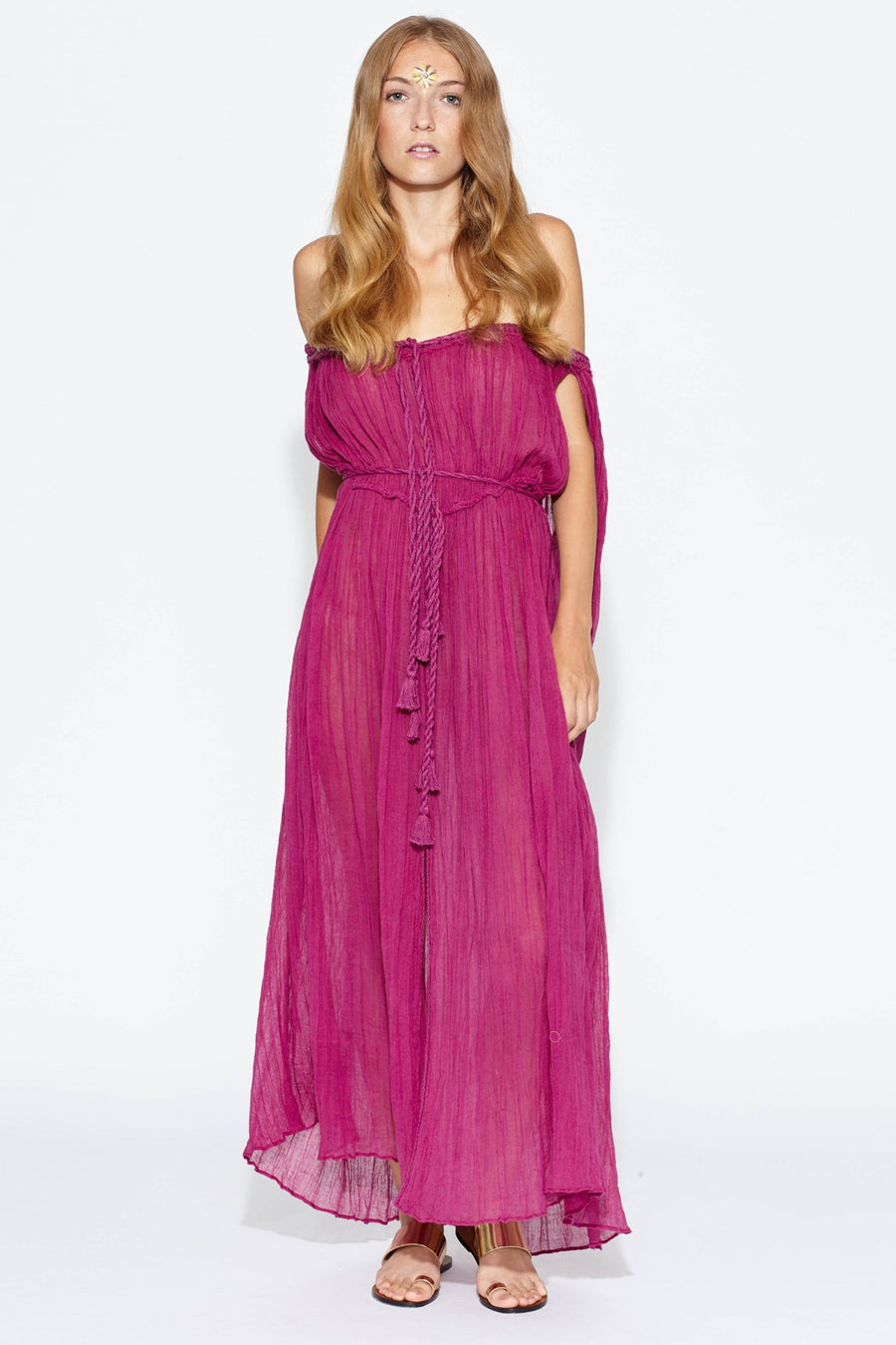 This is a photo of a woman wearing a magenta cotton gauze floor-length maxi coverup that falls off both shoulder and ties around center front chest area and waistline.