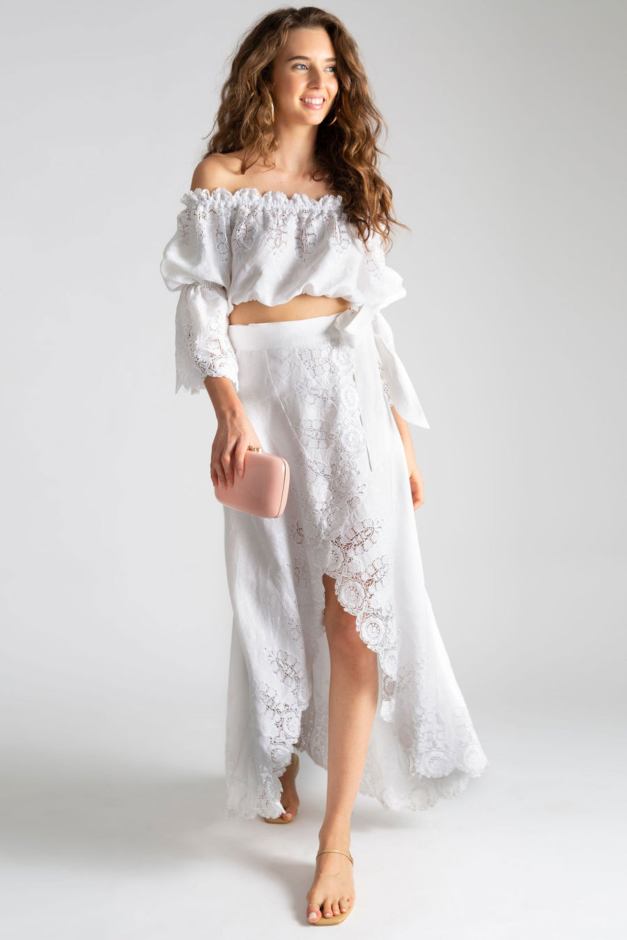 This is a photo of a woman wearing a white linen and lace outfit with maxi wrap skirt open in the front and off the shoulder top with peasant sleeves. She holds a light pink clutch and styles the look with nude sandals.