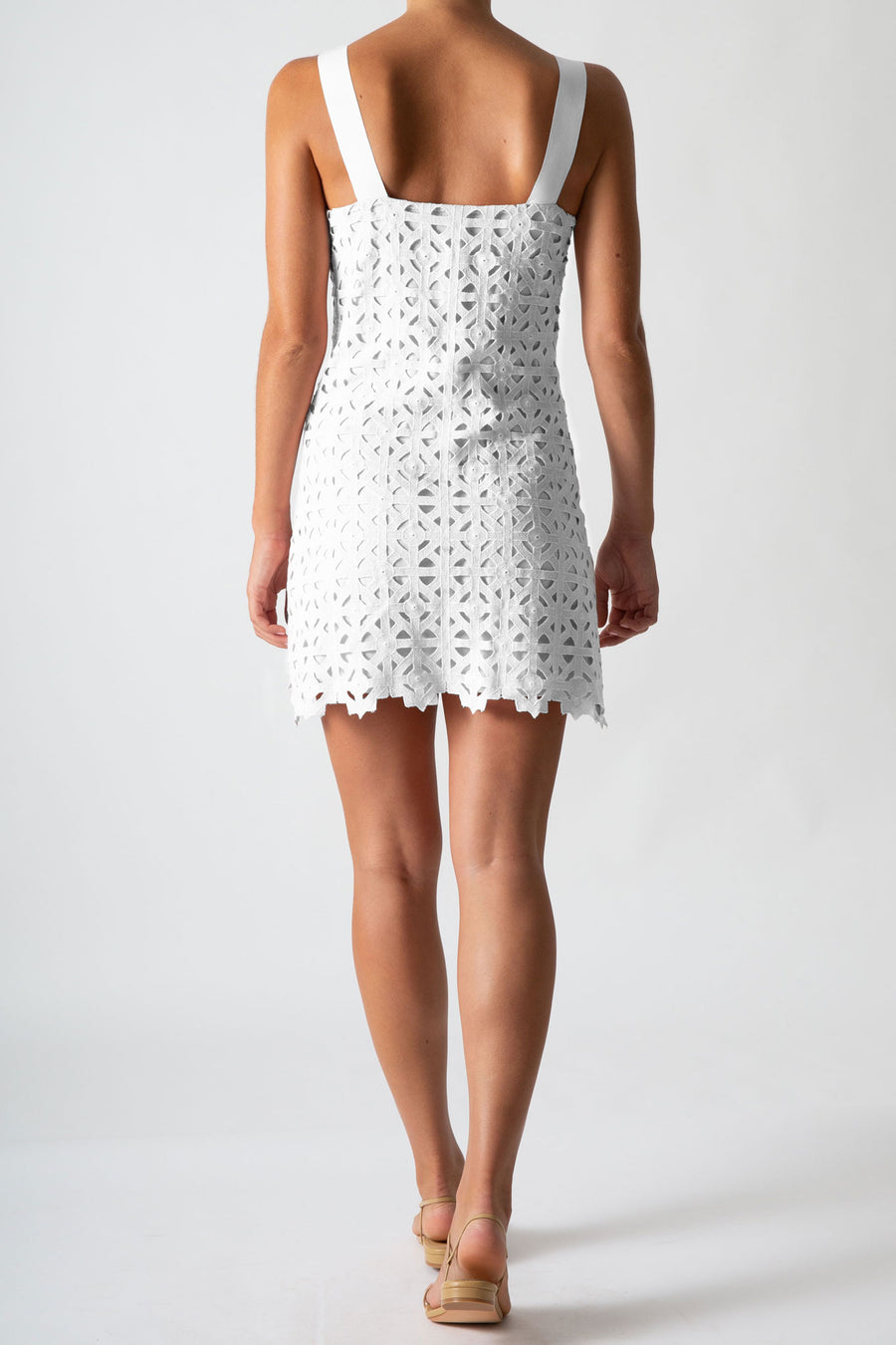 This is a back view photo of a woman wearing a mini white lace dress with ribbon straps.