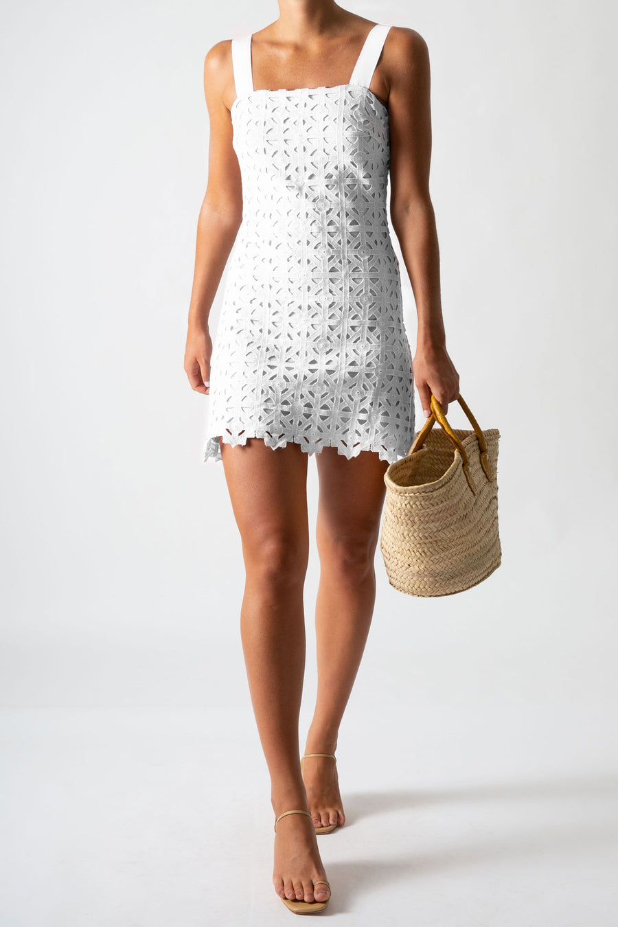 This is a photo of a woman wearing a mini white lace dress with ribbon straps. She holds a basket.