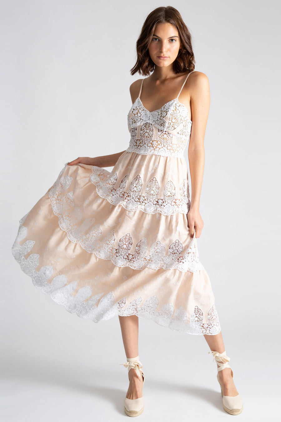 This is a photo of a woman wearing a mid length linen and lace embroidered gown with sweetheart neckline in a honeyglow linen color with white lace embroidery. She holds the right side of the skirt to show 3 tiers of lace and wears the dress with natural colored espadrilles.