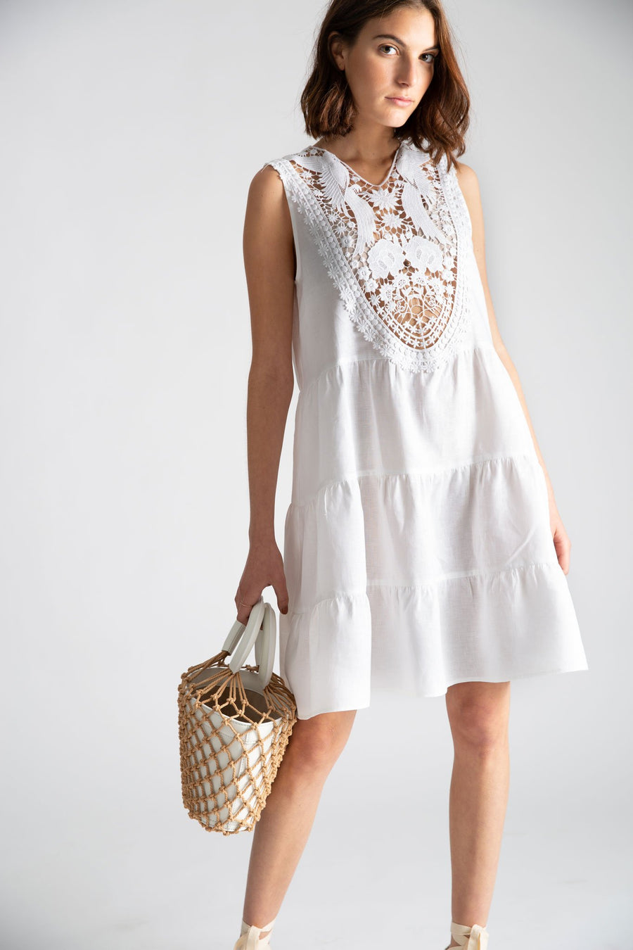 This is a photo of a woman wearing a white linen coverup dress that falls right about her knee and has 3 tiers. The front of the dress has a lace yolk that peeks through to her bikini top underneath. She is holding a white bag with natural netting over it.
