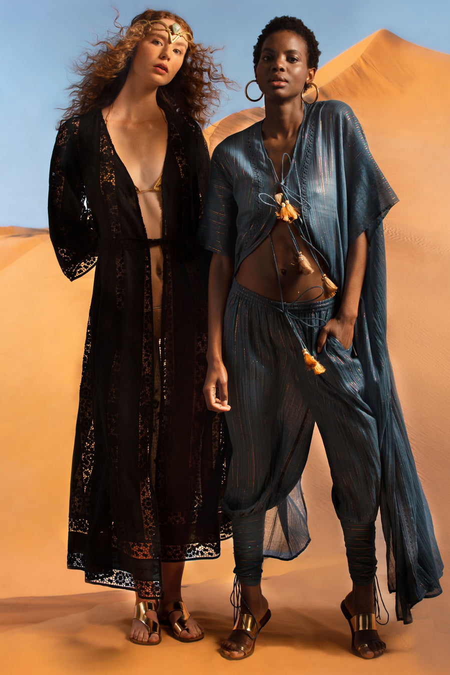 This is a photo of two women standing together. One wears an open black wrap lace coat over a gold bikini and the other wears a blue cotton gauze coat and pants with metallic detailing.