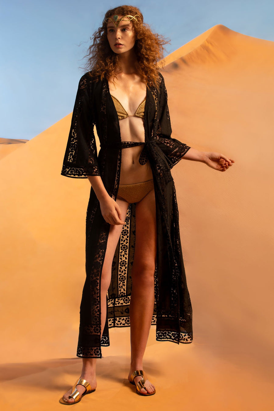 This is a photo of a woman wearing a black lace embroidered coat as a coverup. She wears it open over a gold bikini and gold sandals.