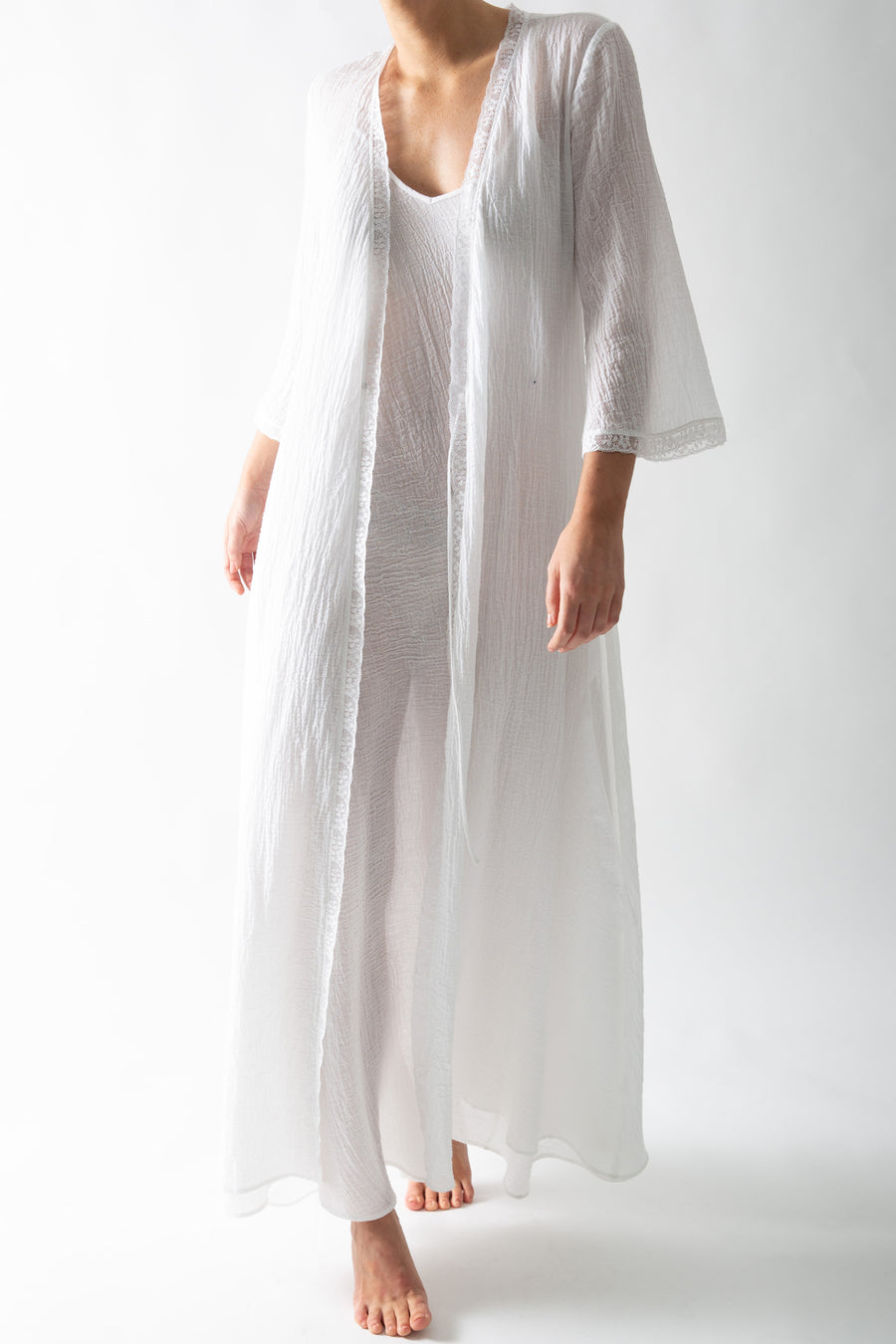 This is a photo of a woman wearing a white cotton gauze rope with wrap closure. There is lace trim along the seams and she wears it open with a white slip dress underneath.