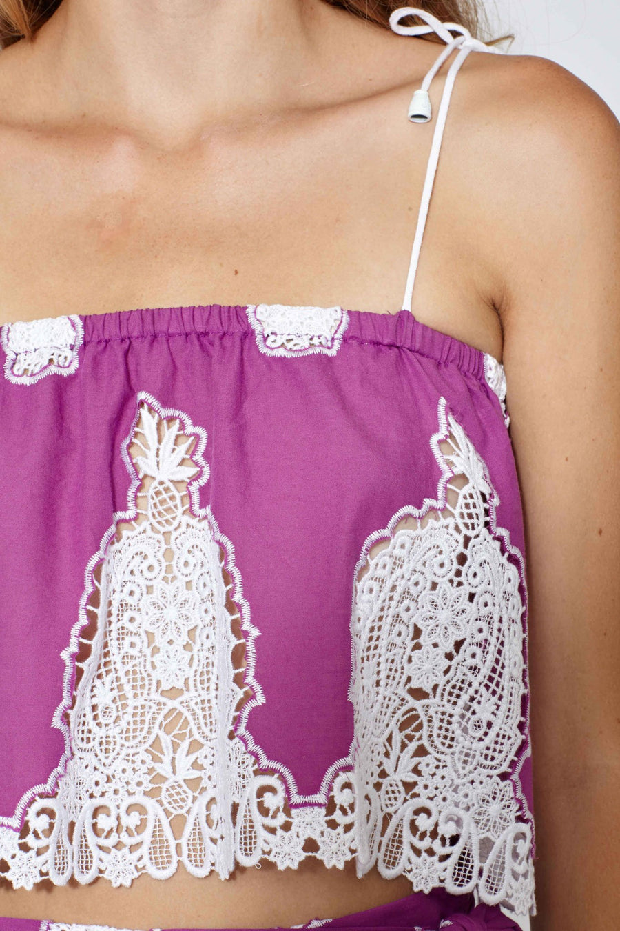 This is a detail photo of a purple cotton crop top with white lace embroidery and white tie straps. Embroidery is paisley-inspired and features a small pineapple.