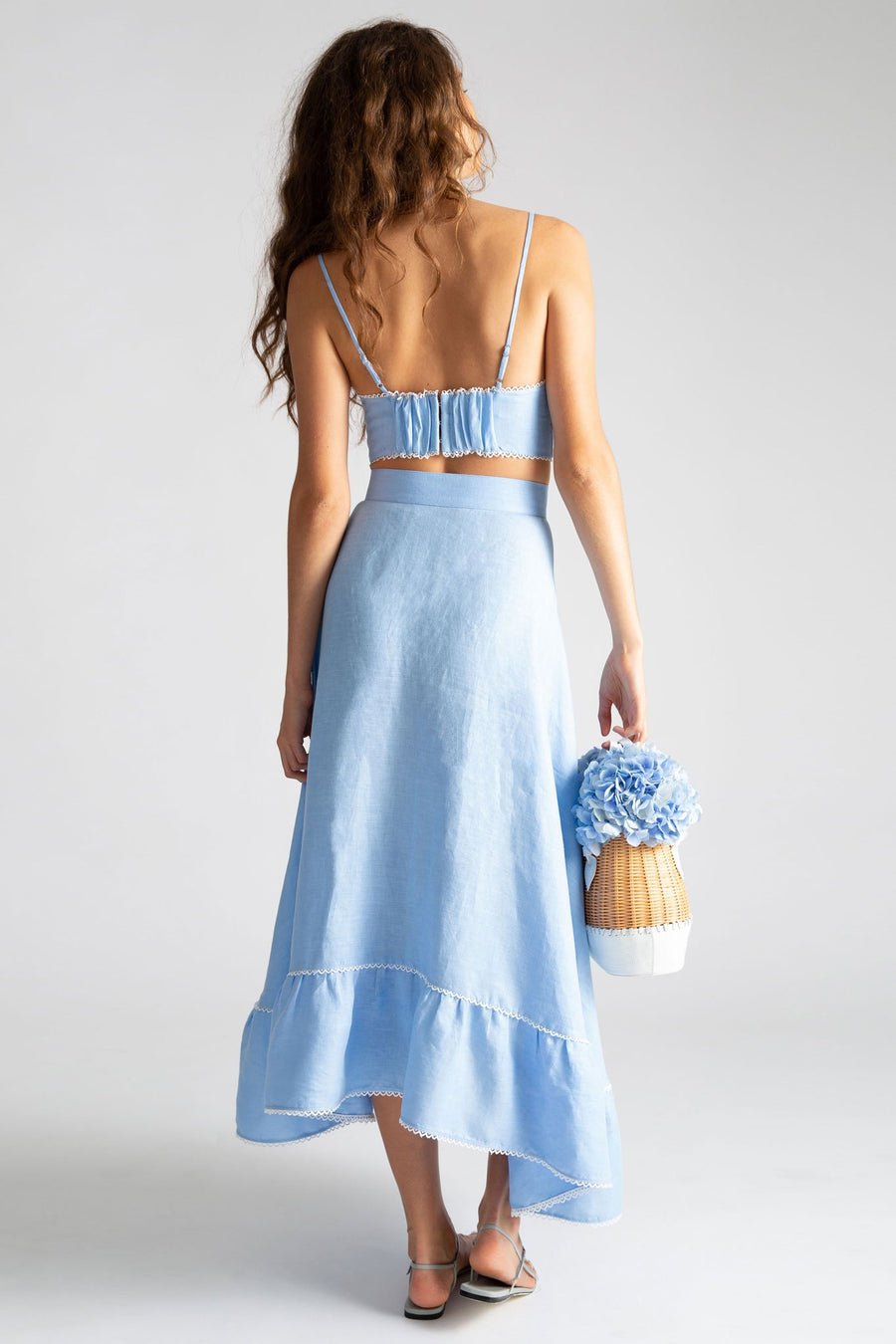 This is a photo of the backside of a woman wearing a light blue linen crop top and wrap skirt. She holds a straw bag with blue flowers in it.