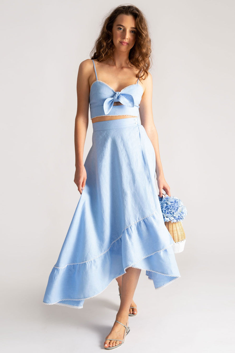 This is a photo of a woman wearing a light blue linen crop top and wrap skirt. She looks over one shoulder and holds a straw bag with blue flowers in it.