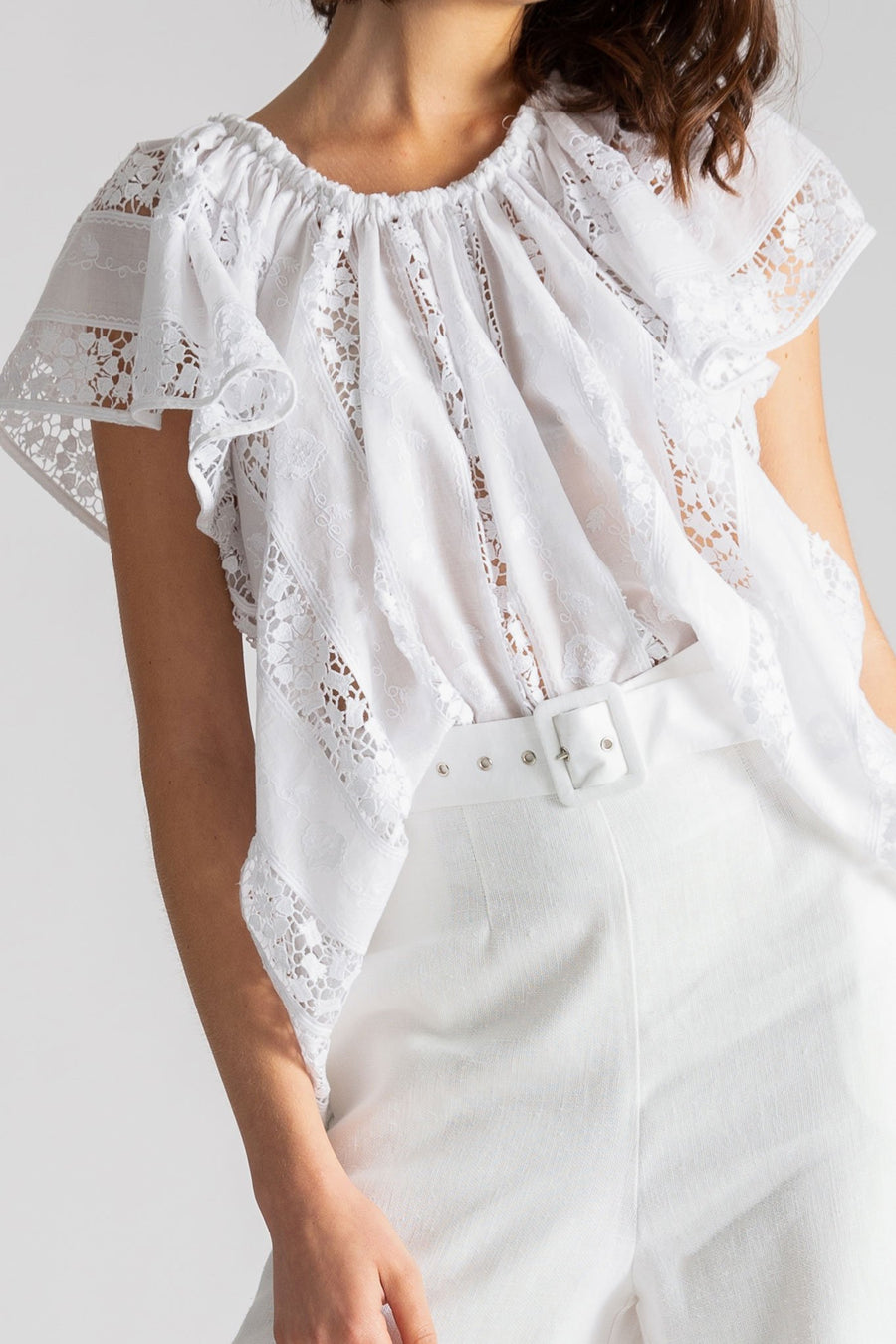 This is a detail photo of the woman's cotton and lace embroidery top with a scoop neck and flowy short sleeve. The top is tucked into white linen pants with a belt.