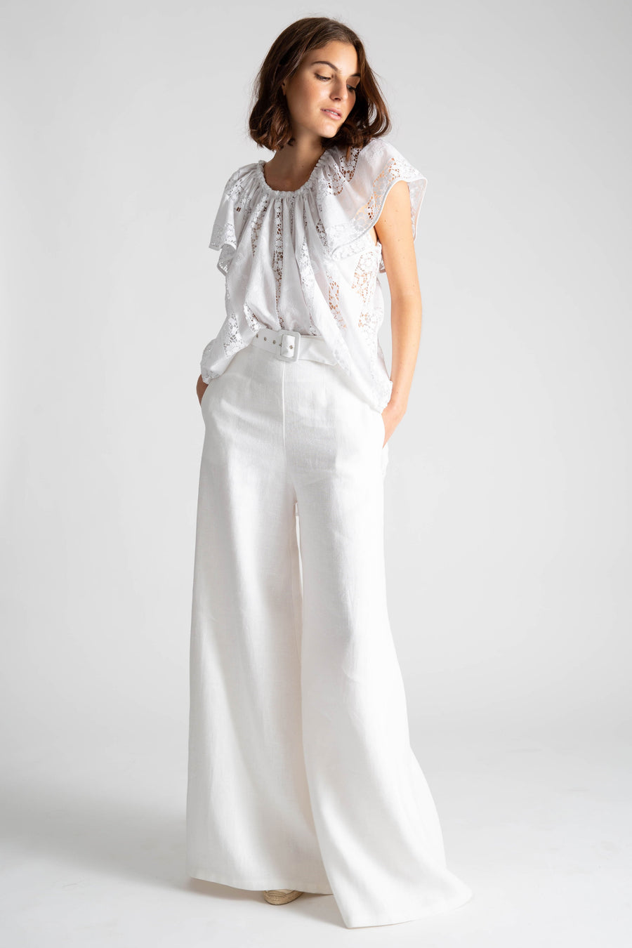This is a photo of a woman wearing an all white outfit with linen white high waisted flare pants and belt. On top, she wears a high-low top with flowy show sleeves in a cotton lace embroidery.