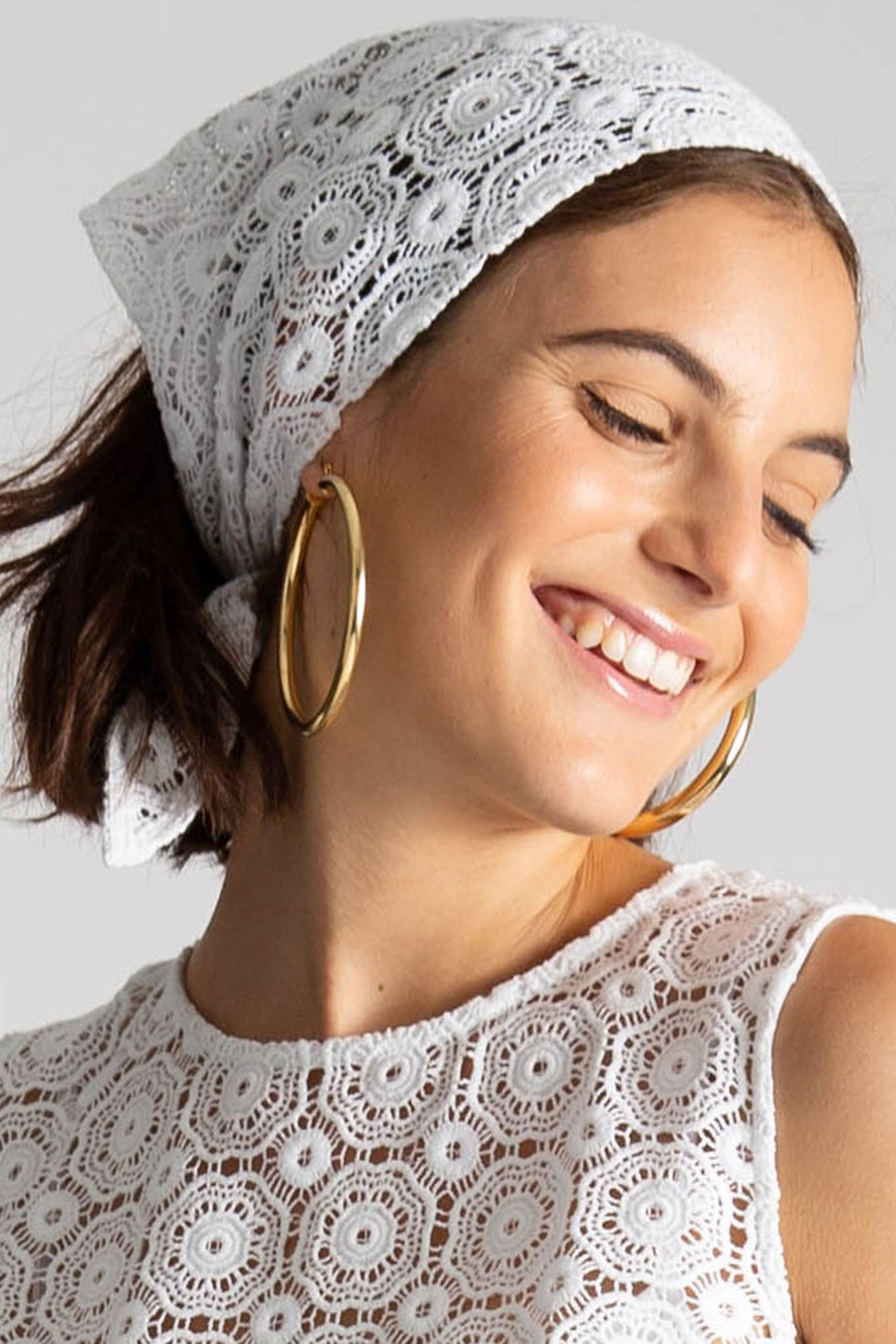 This is a photo of a girl wearing a lace headscarf with gold hoops and matching lace crop top. She smiles and looks over her shoulder.
