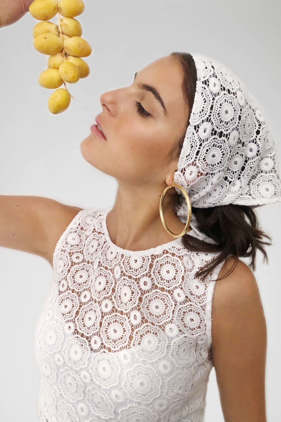This is a photo of a girl wearing a lace headscarf with gold hoops and matching lace crop top. She is holding fruit above her face.