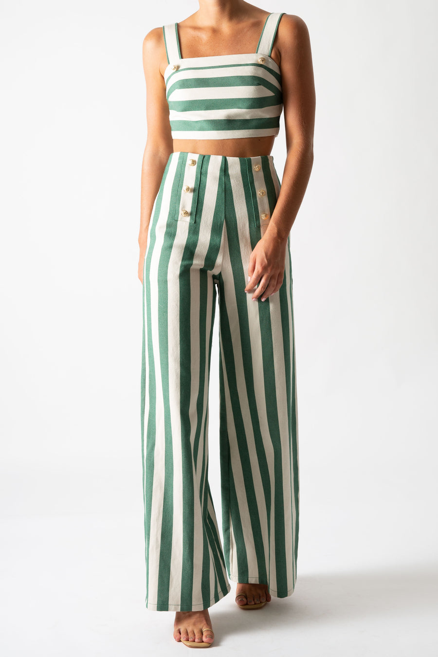 This is a photo of a woman wearing a matching two piece green striped set with gold buttons.  The pants are high waisted and long with a flare and the top is cropped with straps.