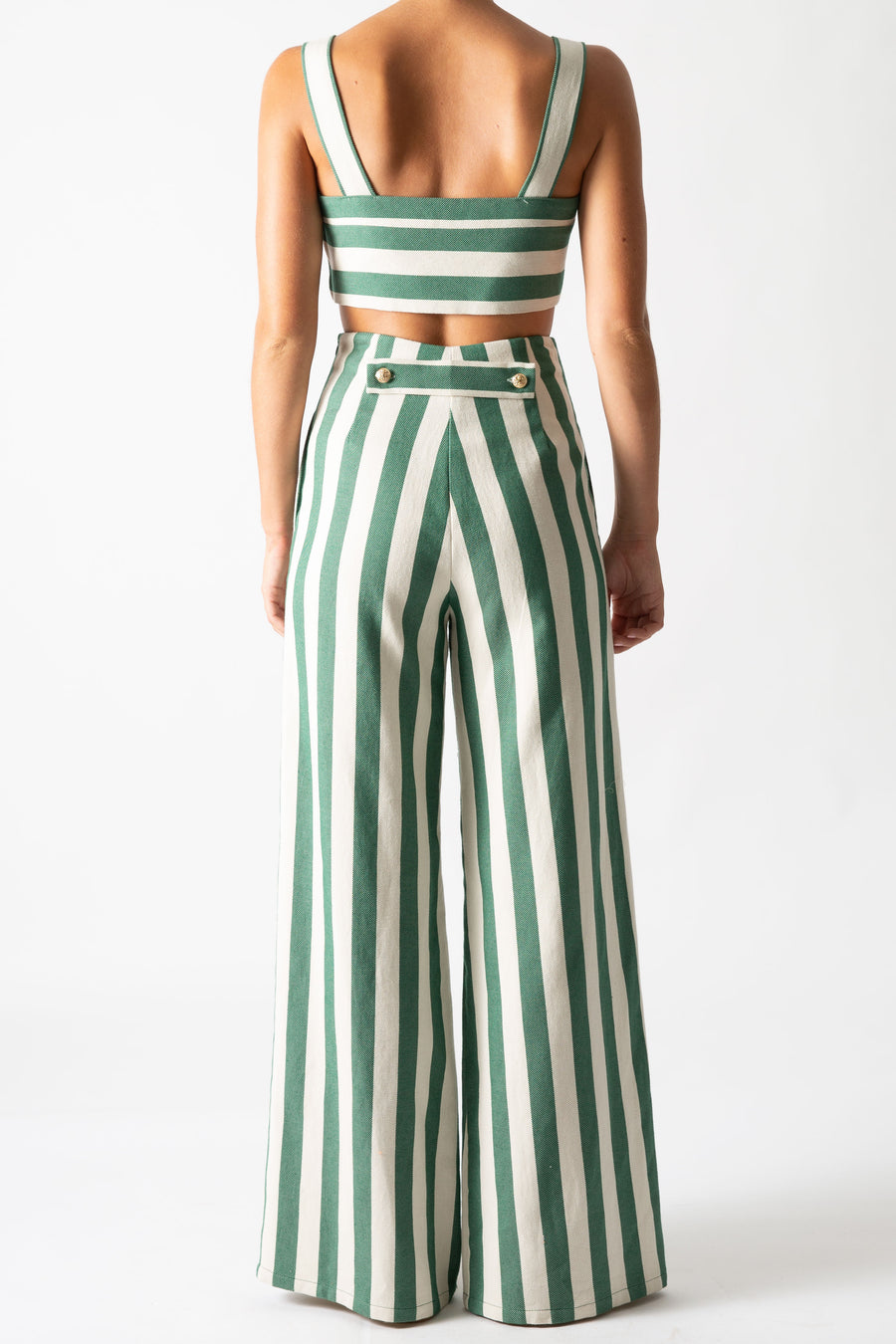 This is a back view photo of a woman wearing a matching two piece green striped set with gold buttons.  The pants are high waisted and long with a flare and the top is cropped with straps.
