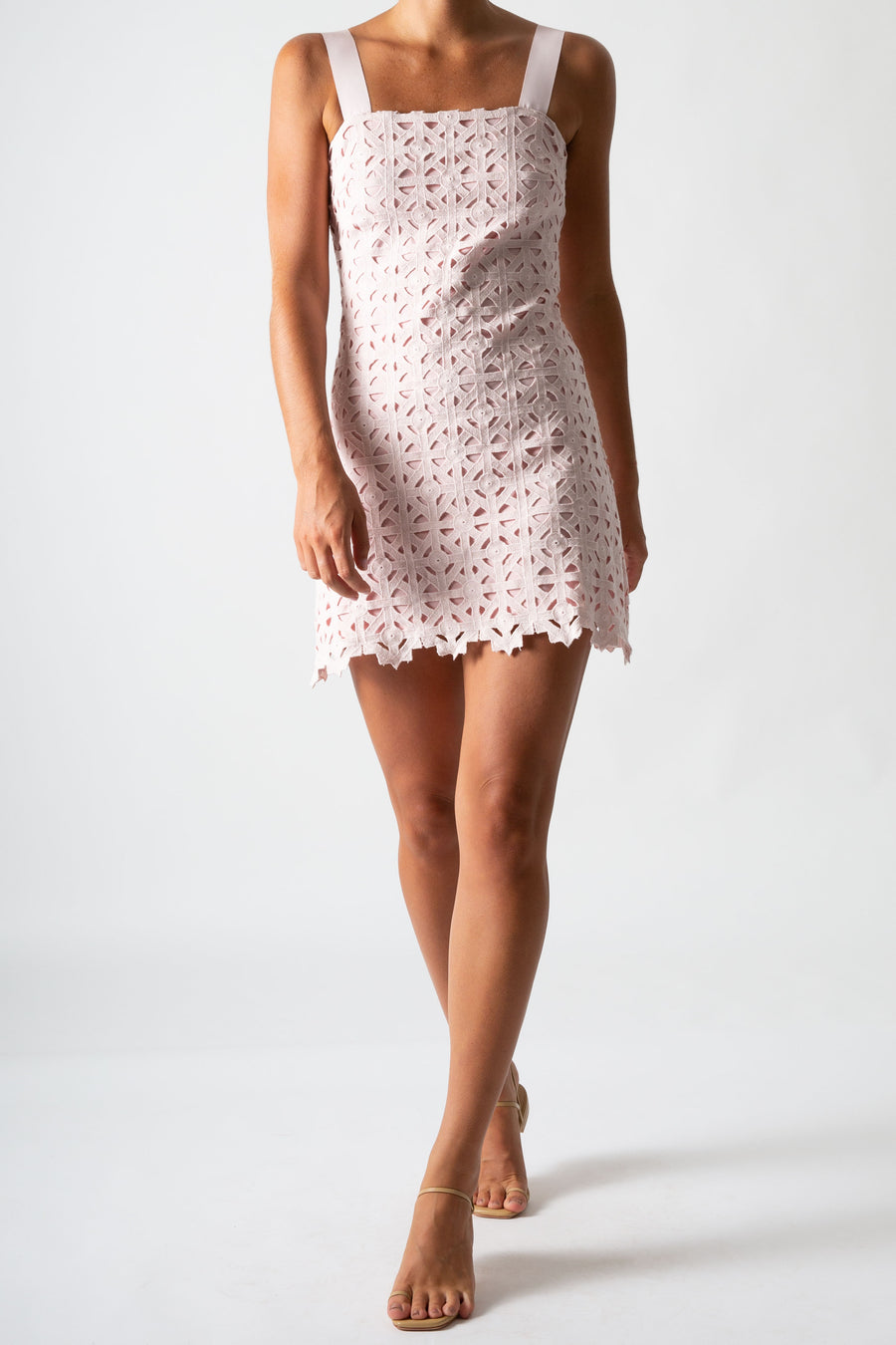 This is a photo of a woman wearing a mini pink lace dress with ribbon straps.