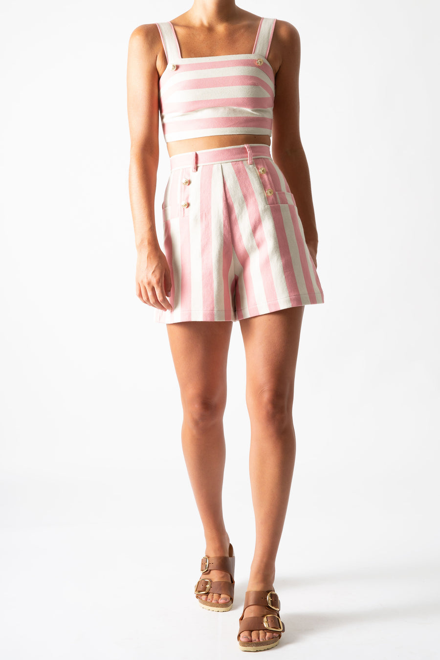 This is a photo of a woman wearing a matching two-piece suit with shorts and a cropped top,. The outfit is pink and neutral thick stripes with gold buttons.