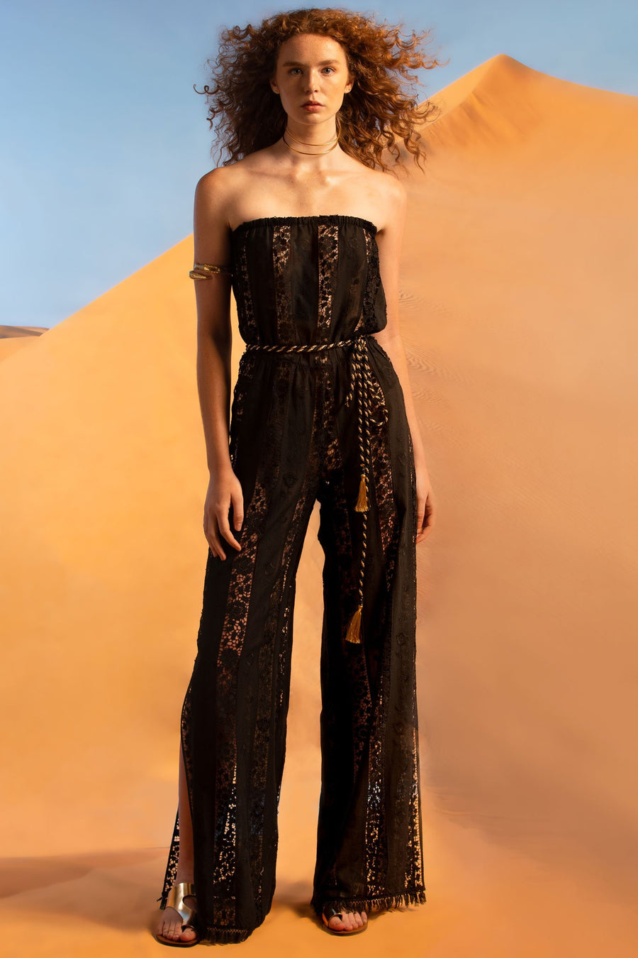 This is a photo of a woman wearing a strapless black cotton and lace embroidered jumpsuit. It has an elastic waistline and side leg slits. The hemline is finished with black fringe and the model wears a gold and black metallic belt around the waist.