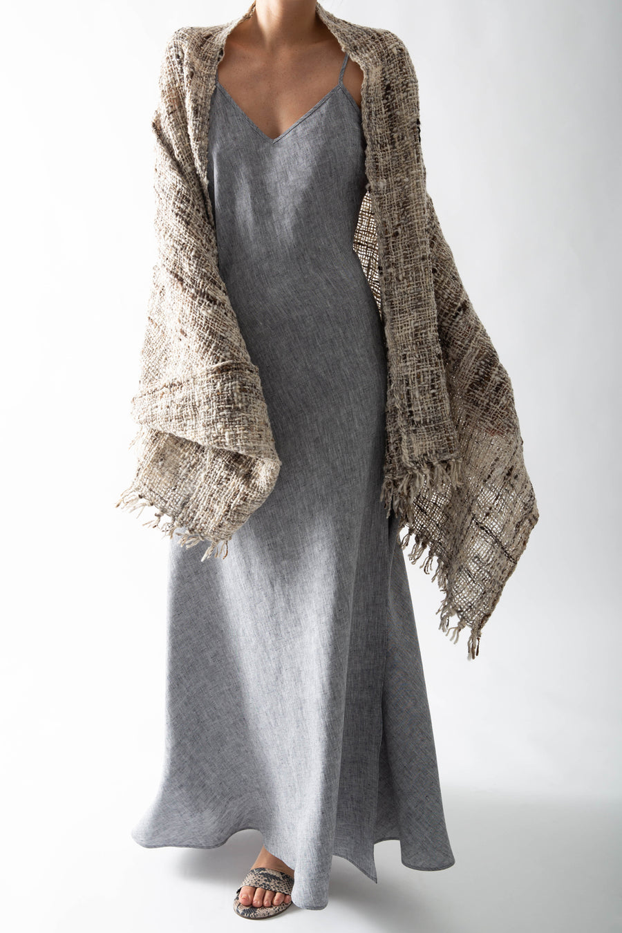 This is a photo of a woman from the neck down. She is wearing a long, woven shawl on top of a linen slip dress. The shawl is multicolored, featuring natural shades of gray, brown, and tan and has fringed tassels along the edges.