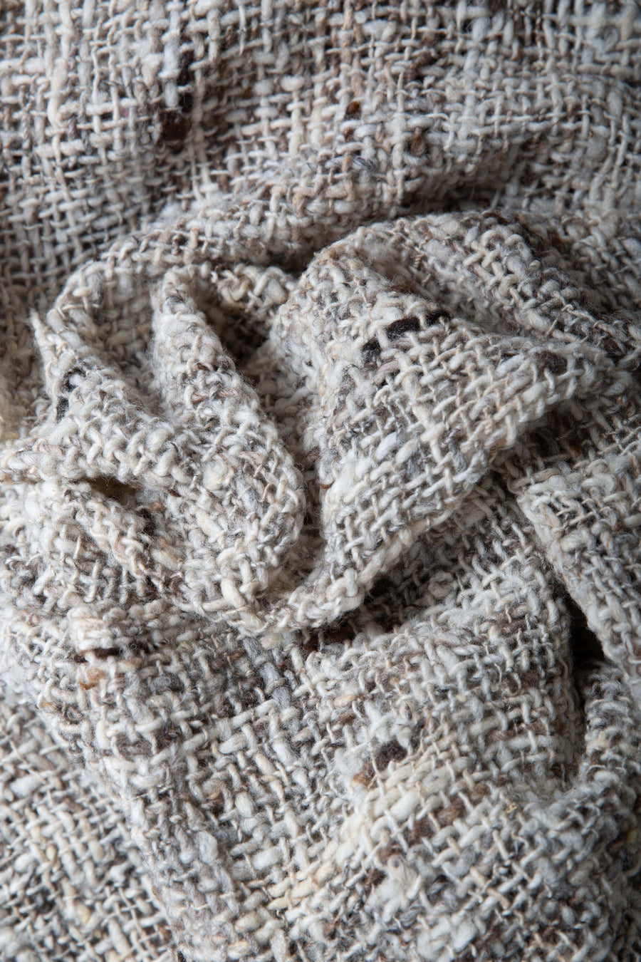 This is a close-up on just the woven shawl, showing the detailed texture of the weave. Each thread is a unique color and thickness.