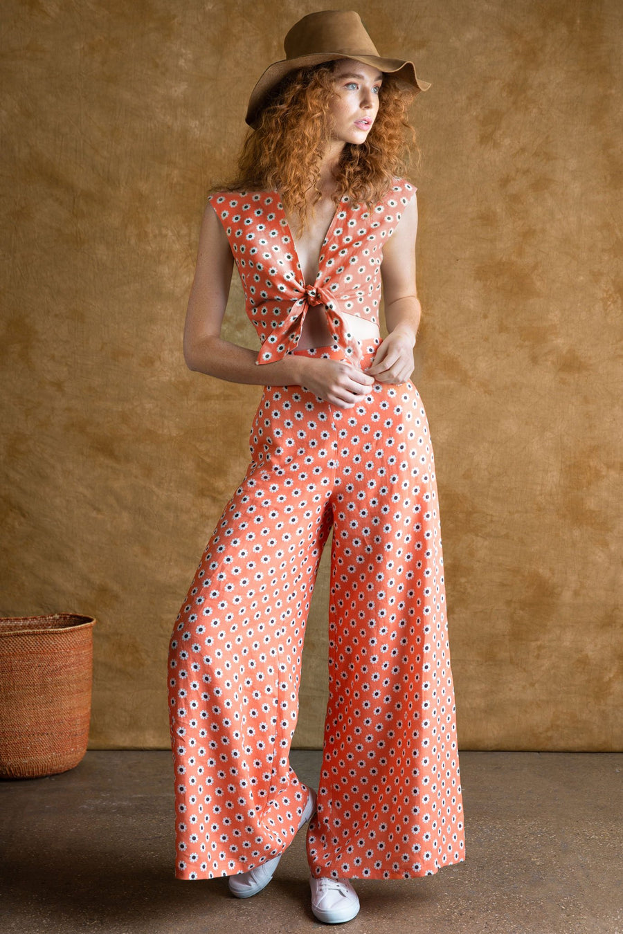 This is a photo of a woman wearing a two piece linen set with deep v neck tied crop top paired with high waisted flare pants. The full outfit is in coral-colored daisy print. The models wears white sneakers and a brown safari hat.