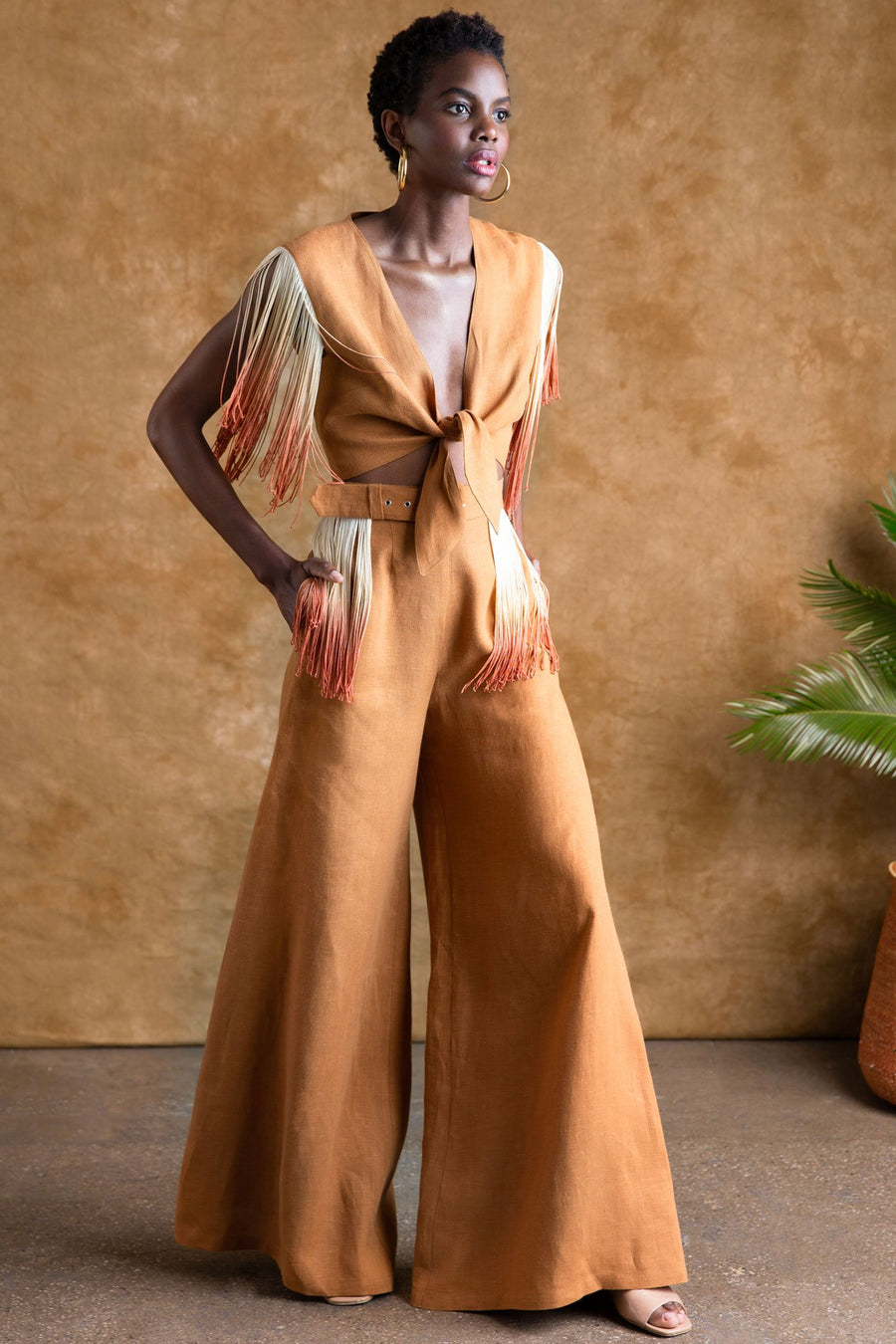 This is a photo of a woman wearing a rust-colored linen 2 piece set. The top is a tie top with a deep v neckline and fringe hanging from the shoulders, as a sleeve. The pants are high waisted with removable belt that has side fringe details that match the top. Model looks to one side with hands in side seam pockets.