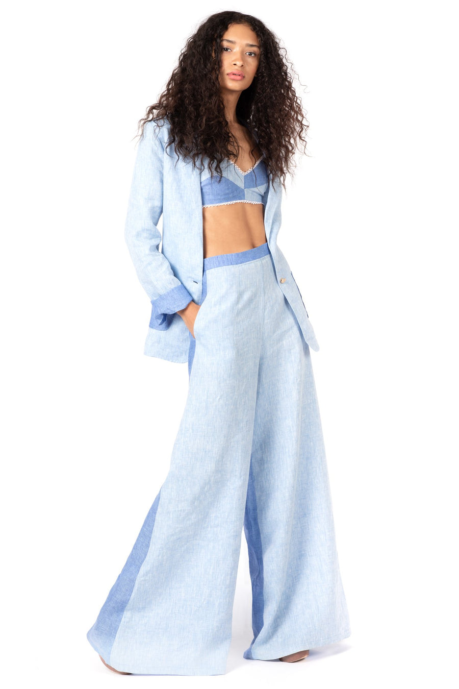 This is a photo of a woman wearing a matching three piece set, inluding a two tone blue linen blazer with a paneled bralette underneath and paired with flare leg pants that are light blue paneled in the front and darker blue paneled at the back.