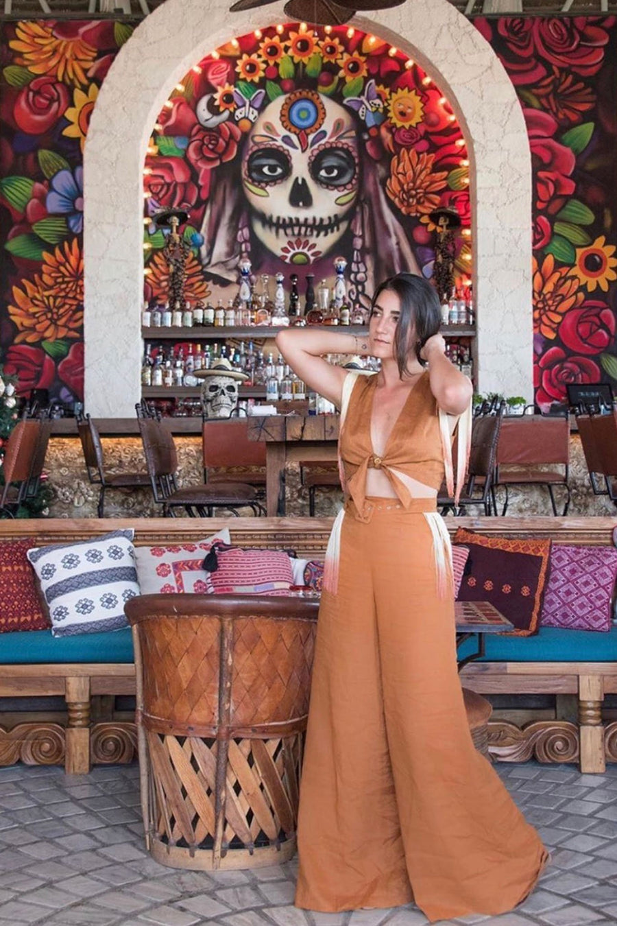 This is a photo of a woman wearing a 2 piece rust-colored linen top and pants with ombre fringe. She is in front of an a wall mural with a skill on it and flowers painted around the skull head.