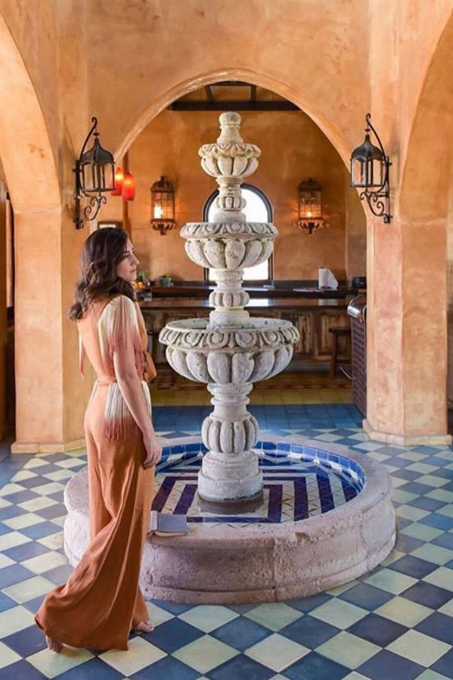 This is a photo of a woman wearing a 2 piece rust-colored linen top and pants with ombre fringe. She is in front of an indoor fountain structure on top of blue and white tile floors.