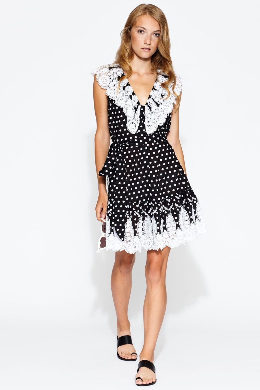 This is a photo of a woman wearing a mini v neck black and white polka dot dress with lace trim on the neckline and bottom hem. It is tied at the waist with a removable black and white polka dot belt.