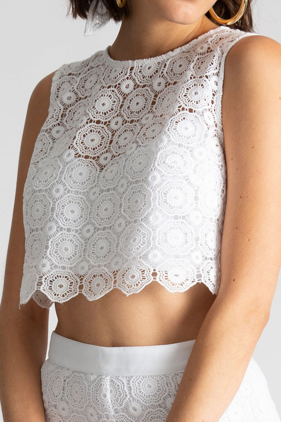 This is a detail photo of an all white lace crop top with white jersey lining and geometric inspired flowers.