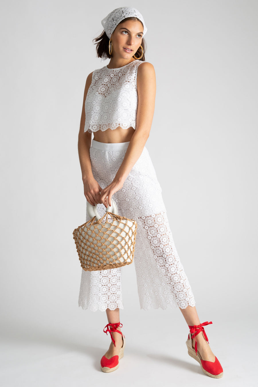 This is a photo of a woman wearing an all white lace outfit with a separate top and cropped pants. She is holding a white bag with natural colored netting around it. She styles the look with a matching lace headscarf, gold hoops, and red espadrilles.