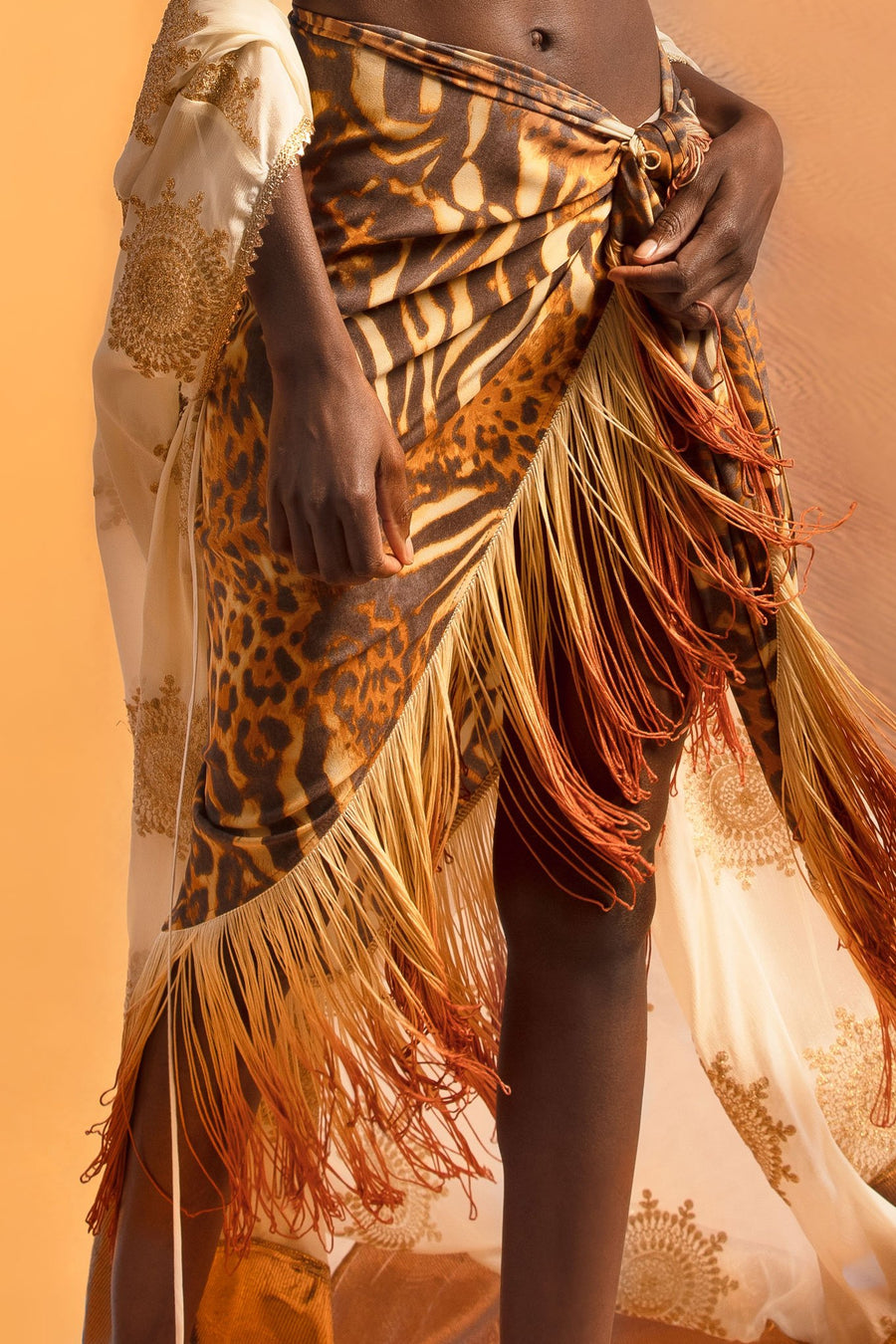 This is a detail photo of a silk cheetah printed pareo with ombre fringe on the hemline.