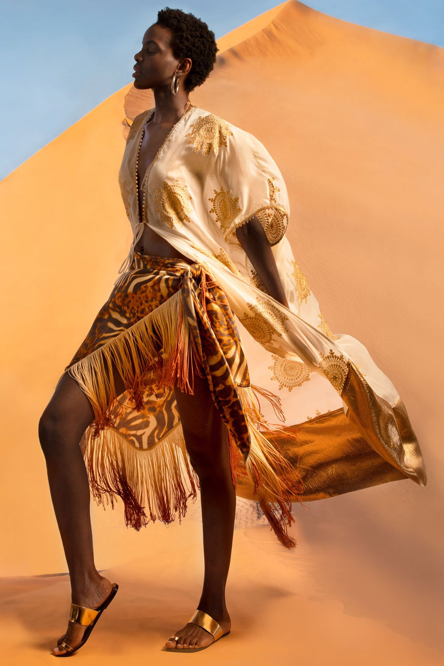 This is a photo of a woman wearing a cheetah pareo with ombre fringe on the hemline. On top, she wears a white coat with gold embellishments and a gold hemline. She stands in front of a desert sand dune.