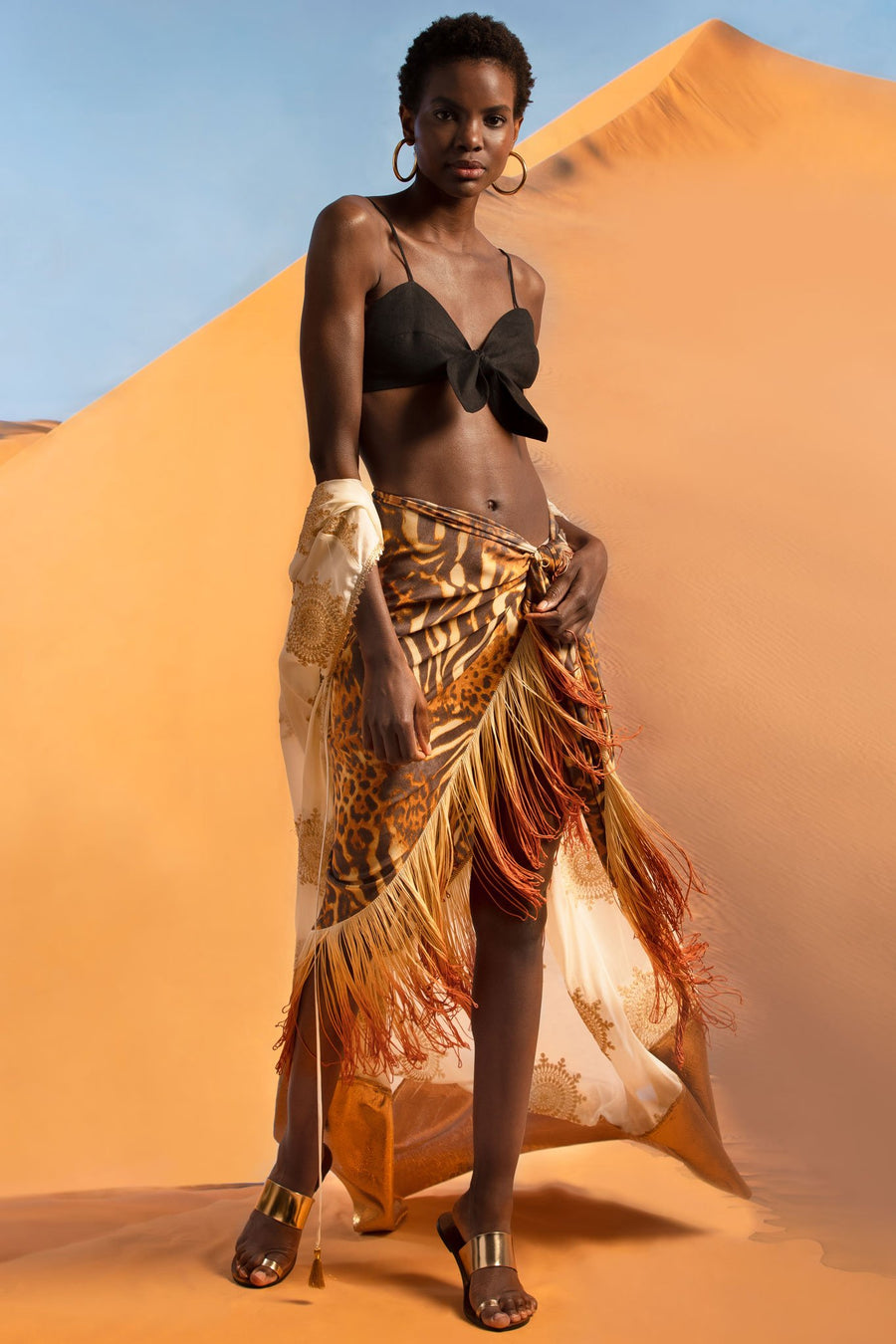 This is a photo of a woman wearing a black linen bralette with center tie, paired with a cheetah pareo with ombre fringe on the hemline. Falling around her arms, she wears a white coat with gold embellishments and a gold hemline. She stands in front of a desert sand dune.