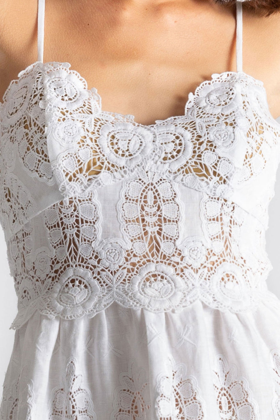 This is a detail photo of the top of a white linen and lace dress with a sweetheart neckline. The lace details show flowers and dragonflies.