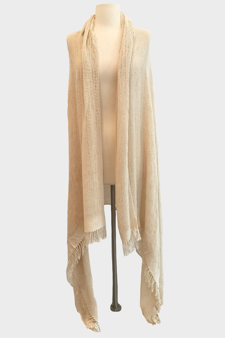 This is a photo of a natural-colored shawl on a mannequin. The shawl is open in the front and falls to the floor at the longest point.