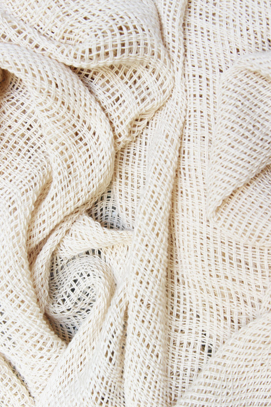 This is a detail photo of the texture of a handmade knit natural-colored shawl.
