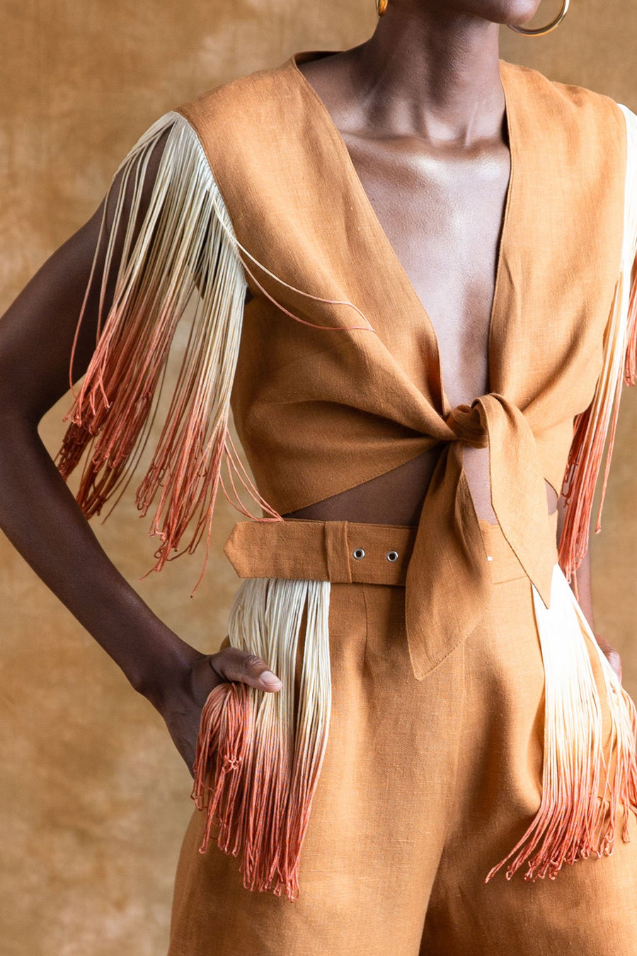 This is a detail photo of a 2 piece rust-colored linen set with ombre fringe on the shoulder of the top and the removable belt of the pant.