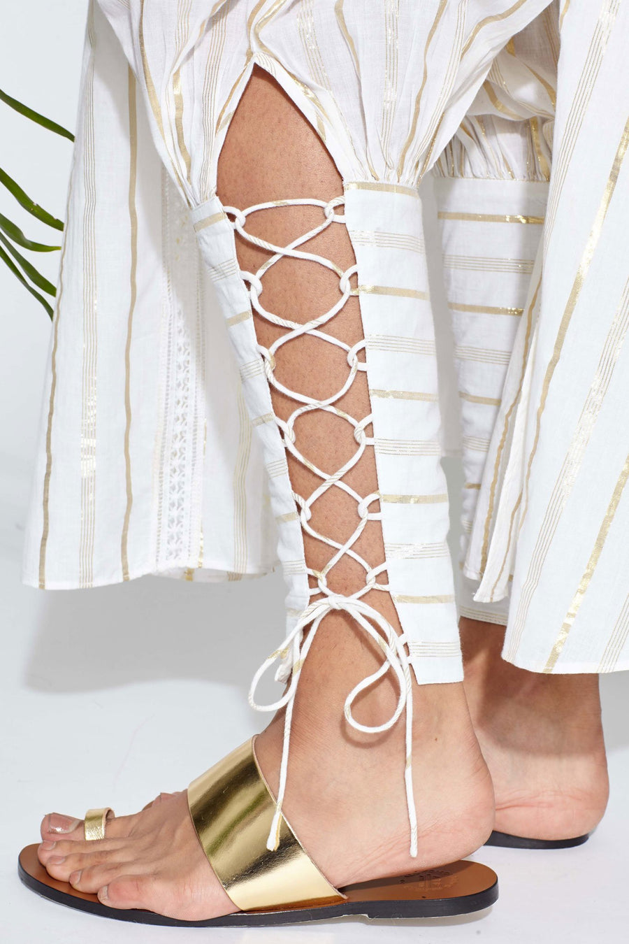 This is a detail photo of white colored pants with metallic gold stripes and a lace up detail from the ankle to calf on the pant leg. Model wears gold sandals.