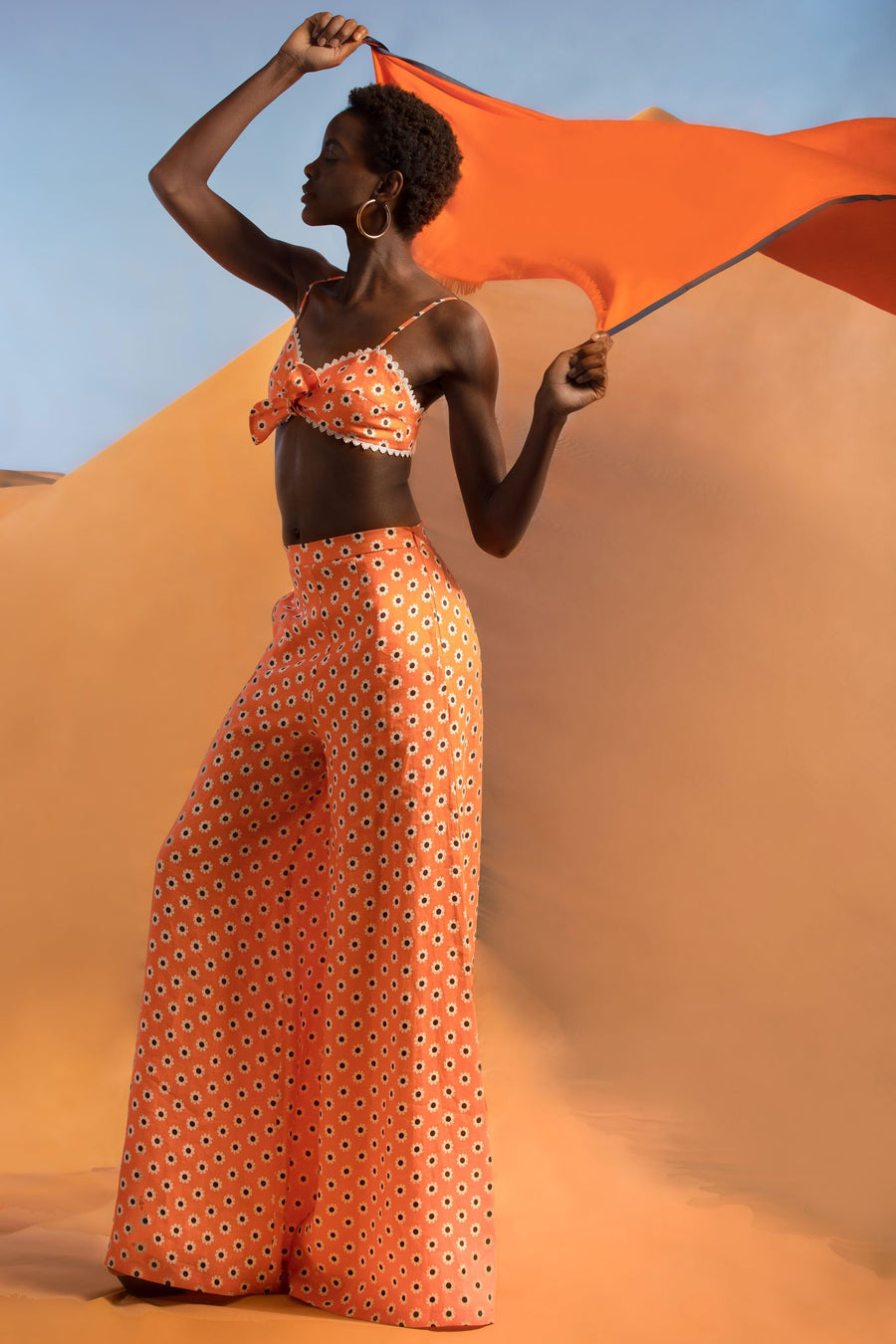 This is a photo of a woman wearing a two piece daisy printed bralette and flare pant in coral color. She holds an orange scarf blowing behind her and looks to one side.