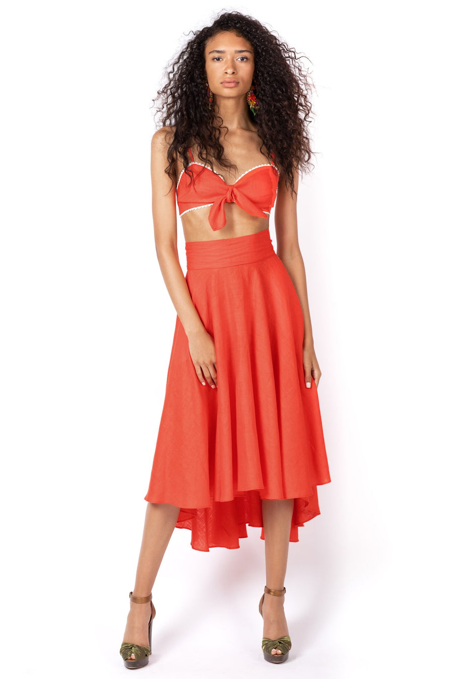 This is a photo of a woman wearing a bright red, crochet trimmed, tie front, linen bralette. Paired with a matching bright red, calf length, linen skirt.